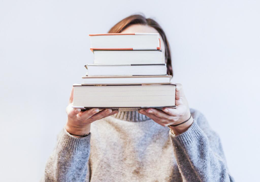Imparare le lingue straniere: una ragazza tiene in mano una pila di libri