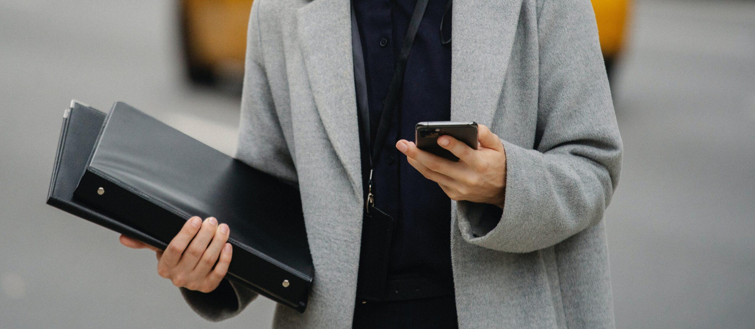 Un Project Manager al lavoro tiene in mano appunti e smartphone