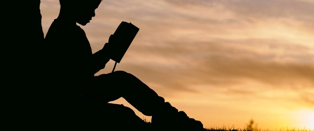 Bambino che legge al tramonto