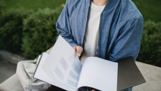 Un ragazzo tiene in mano un quaderno