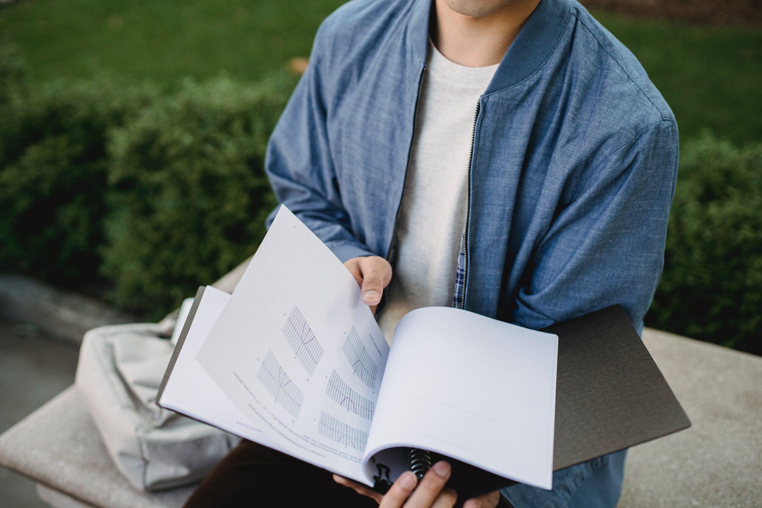Imparare una nuova lingua: un ragazzo tiene in mano un quaderno di appunti