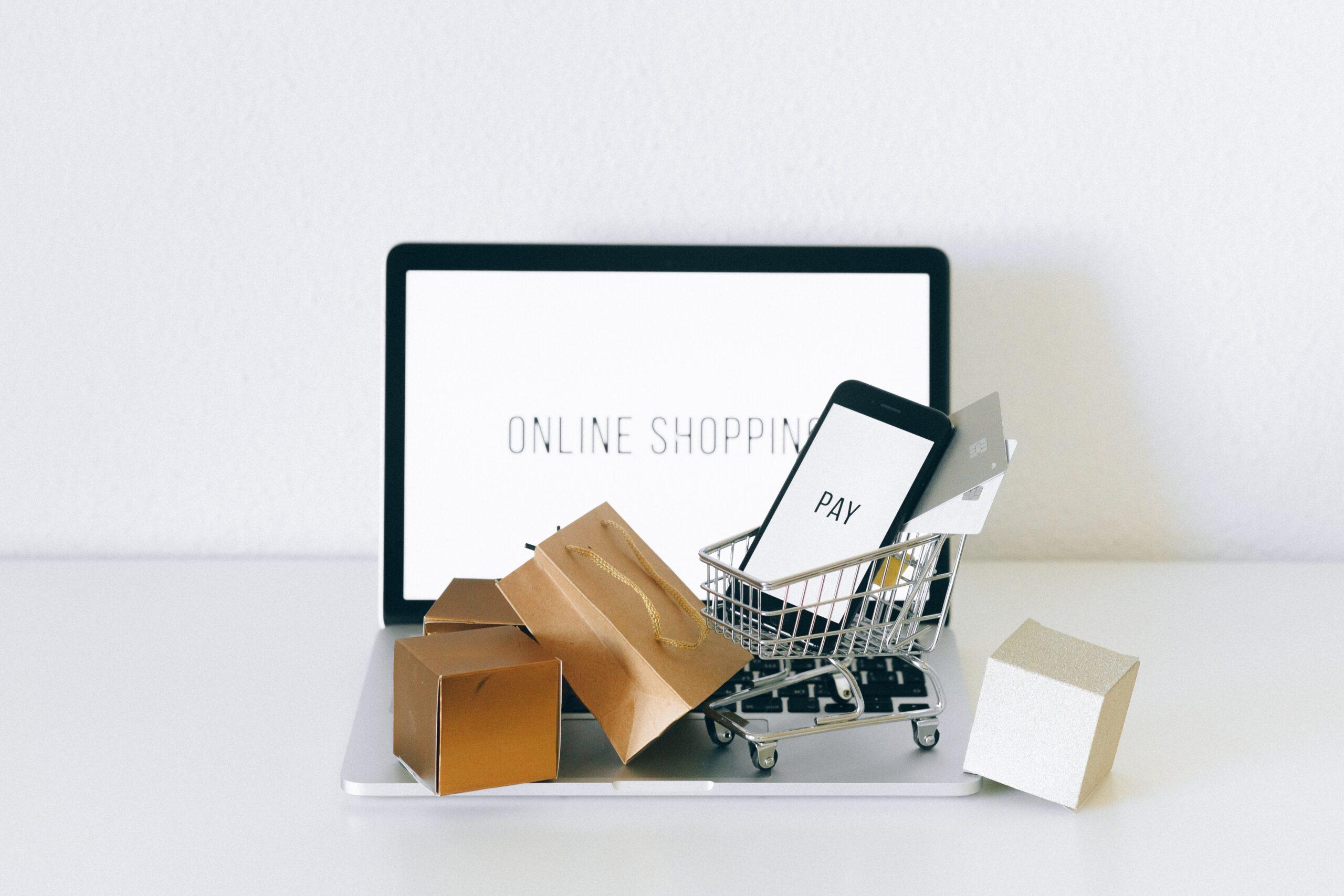 E-commerce: un computer sommerso da sacchetti per lo shopping