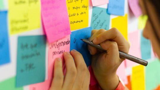 Un bambino scrive su un post it attaccato alla parete