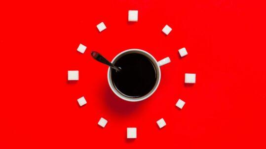 Tazzina di caffè entro una cornice di zollette di zucchero